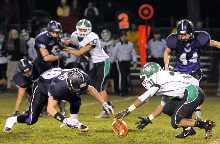 Anthony Franco of North Branford, left, recovers a first-quarter fumble by Anthony Carter of Northwest Catholic during the first quarter of the Class S quarterfinals Tuesday. Photo by Peter Hvizdak / New Haven Register.