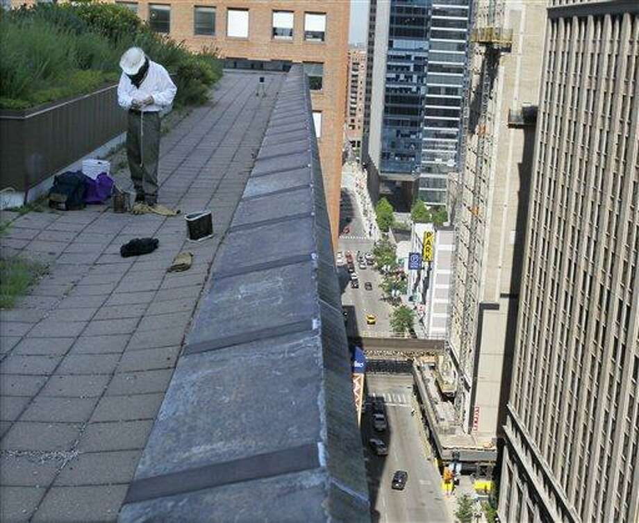 In this photo taken Tuesday, July 12, 2011, beekeeper Michael Thompson prepares to examine a bee hive of over 1000,000 bees high above Randolph Street on the roof of City Hall in Chicago.  The Chicago bees' success could be due to the city's abundant and mostly pesticide-free flowers. (AP Photo/Charles Rex Arbogast) Photo: ASSOCIATED PRESS / AP2011