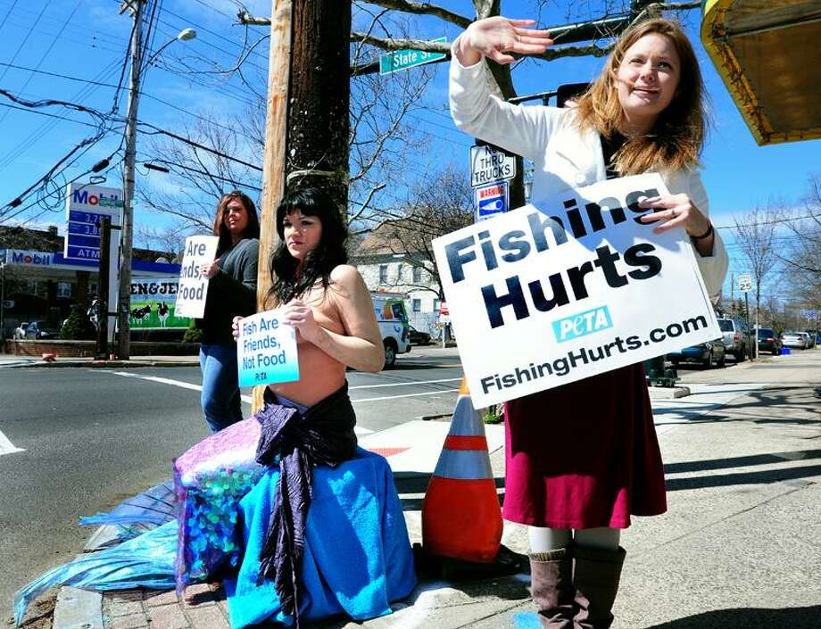 (Left to right) Ryan Gallo of Meriden, Melissa Sehgal of Boston dressed as a topless mermaid and PETA campaigner Lauren Stroyeck protest against eating fish at State and Humphrey streets in New Haven on Tuesday. Photo by Arnold Gold/New Haven Register