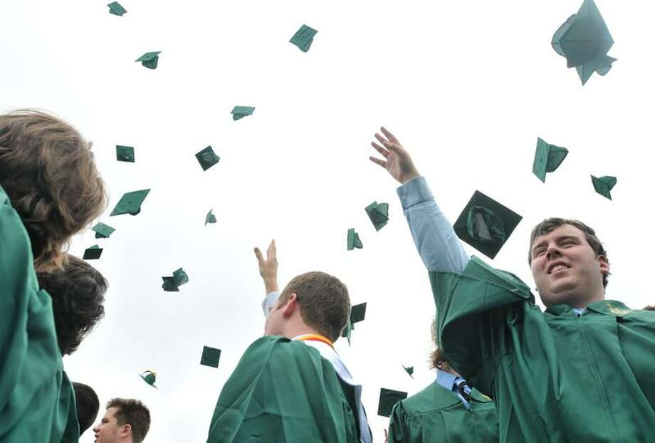 West Haven-- Teddy Malloy, of Derby, right, throws his mortar board in the air with his Notre Dame-West Haven graduating classmates Sunday morning following commencement.  Photo by Brad Horrigan/New Haven Register-05.29.11.