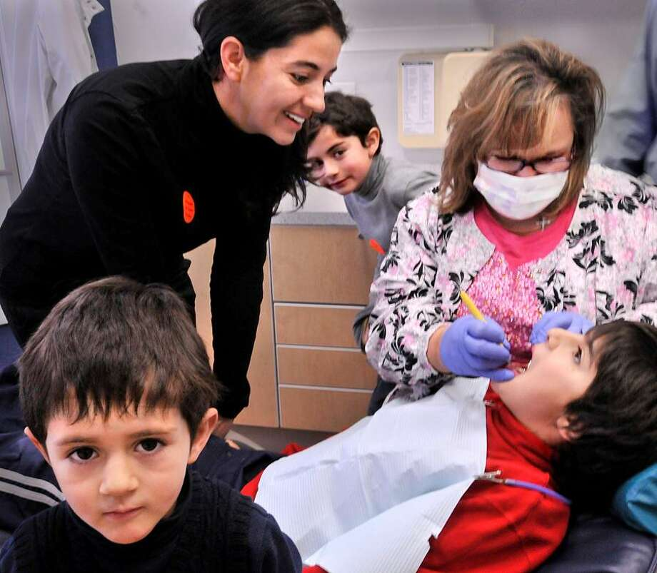 NEW HAVEN_Nora Bernal looks on as her son,  John Paul Rodriguez,9, gets his teeth cleaned at the free clinic taking place at the Levy Dental group office in New Haven. In front is Gabriel Rodriguez ,4. In back is  David Rodriguez,8.  Bernal's husband is a Yale music student.    Melanie Stengel/Register1/29/11