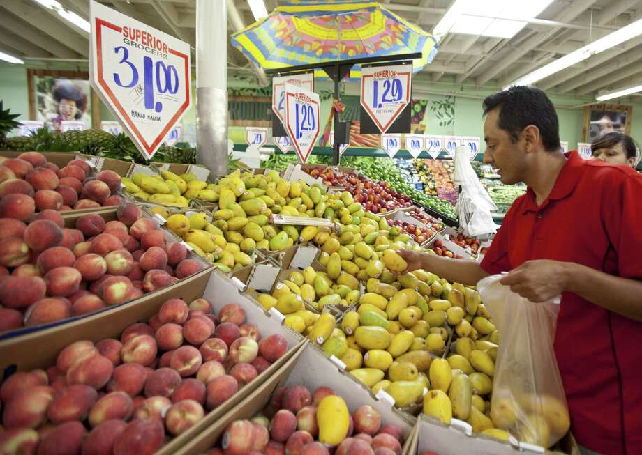 In this May 23 photo, customer Gabriel Sanchez shops for fresh fruit at a Superior Grocers store in Los Angeles. Consumers spent more in April but much of the increase was eaten up by higher food and energy prices. (AP Photo/Damian Dovarganes) Photo: AP / AP