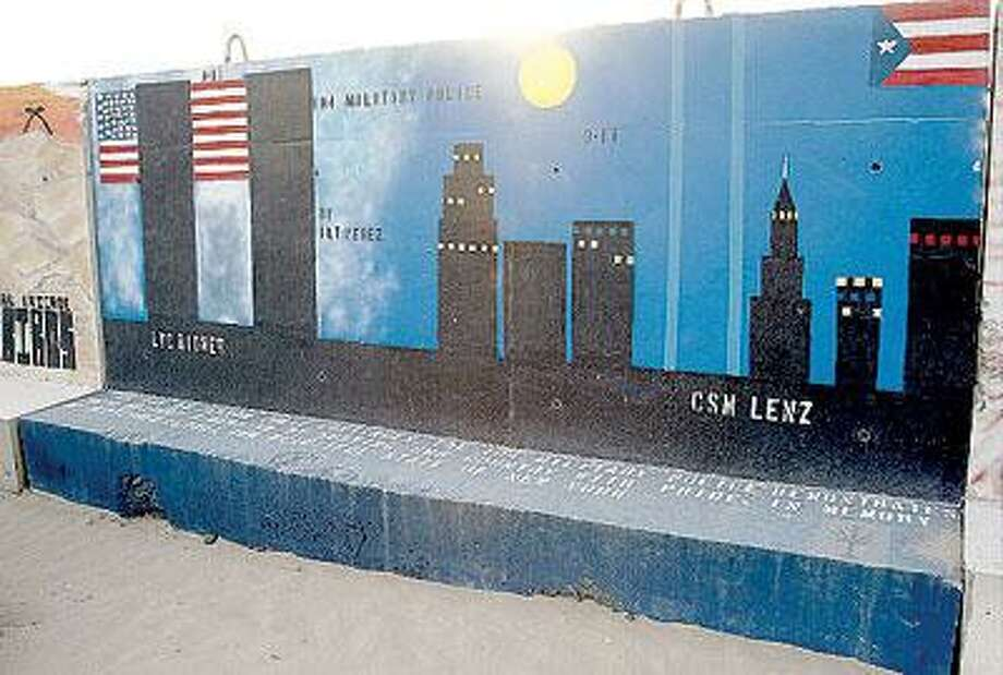 "Photos from George Hauer's book ""The T-Walls of  Kuwait and Iraq,"" which documents the grafitti and  artwork made by soldiers in the field. Different units  each decorate the ""T-walls,"" which surround the  base at Camp Buehring. For example, the 104 Military  Police Unit panel, above, features the New York  skyline and the World Trade Center. (Contributed)"