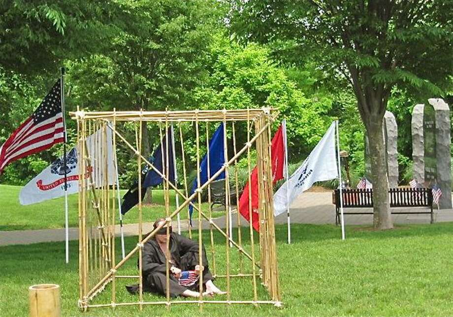 Vietnam veteran Rich Boisvert of West Haven sits in a replica prisoner of war cage at the Veterans Memorial in Shelton Saturday, part of a vigil sponsored by No Vet Left Behind Inc. of Ansonia. Patricia Villers/Register