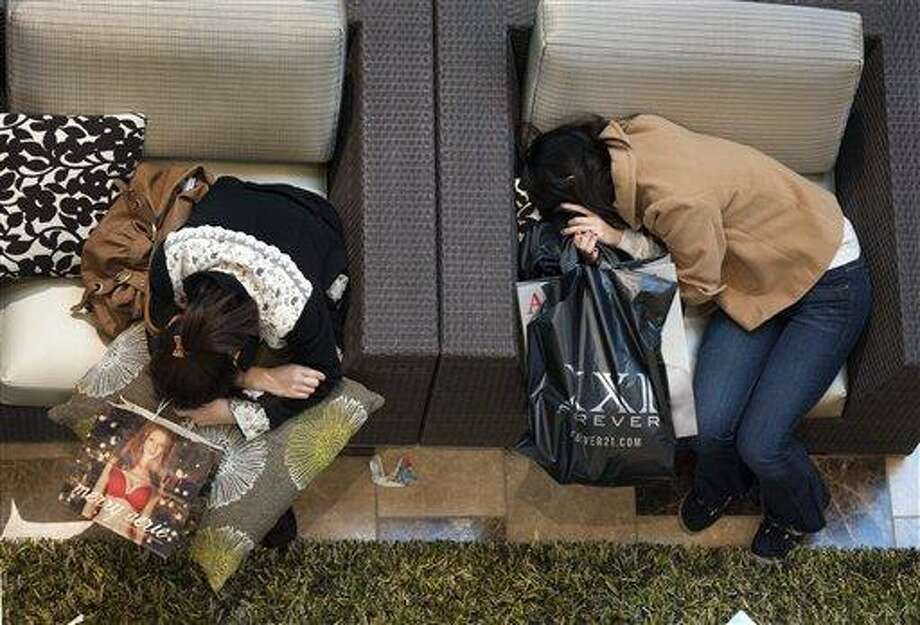 Black Friday shoppers take a rest at Westfield Galleria at Roseville in Sacramento, Calif., on Friday, Nov. 25, 2011. (AP Photo/The Sacramento Bee, Hector Amezcua) Photo: ASSOCIATED PRESS / AP2011