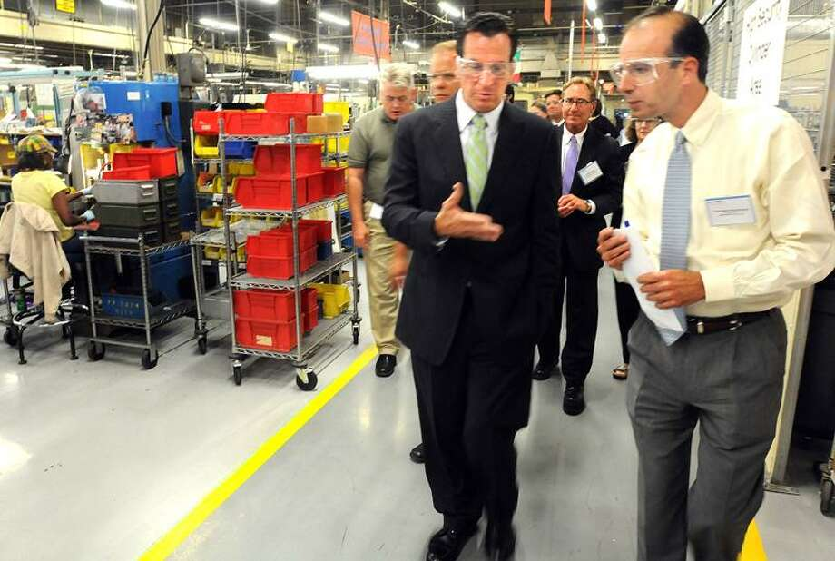 Gov. Dannel P. Malloy, left, tours the Assa Abloy plant in New Haven Thursday with Assa Abloy President and CEO Thanasis Molokotos, right. Mara Lavitt/Register