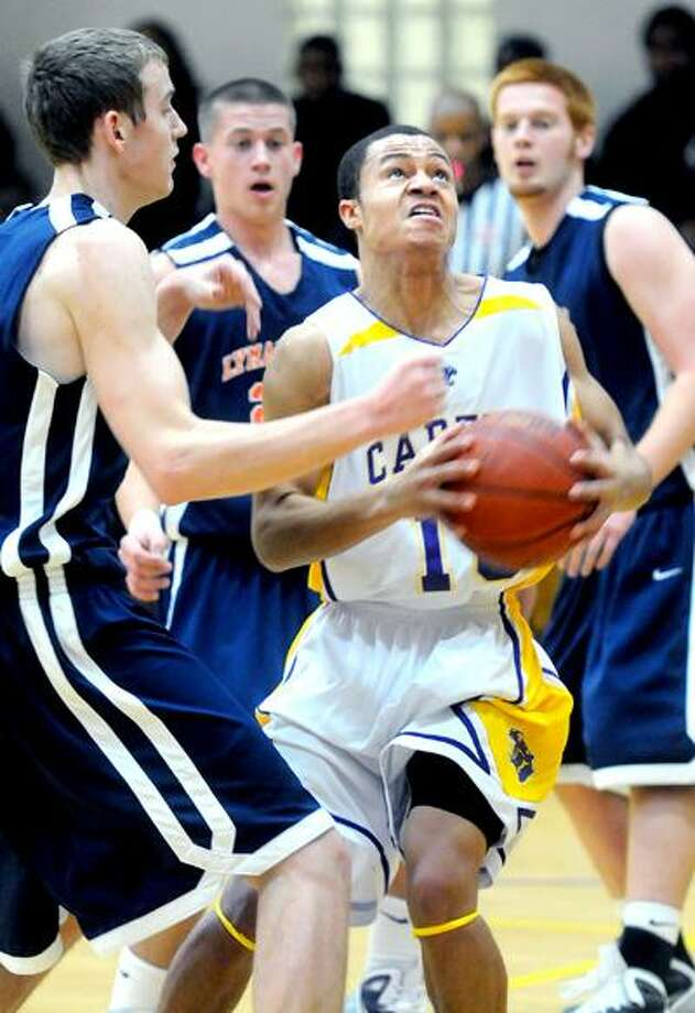 Brandyn Benson (center) of Career drives past Jason Dempsey (left) of Lyman Hall in the first half at Career High School in New Haven on 1/28/2011.  Career won 57-55. Photo by Arnold Gold/New Haven Register      AG0401C