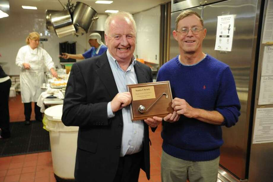 Christy Mulhall, left, of Christy's Irish Pub in New Haven, and David O'Sullivan, director of the Community Soup Kitchen in New Haven, hold the Golden Ladle plaque, given to Mulhall for his fund-raising efforts for the soup kitchen over the past five years.VMWilliams/Register