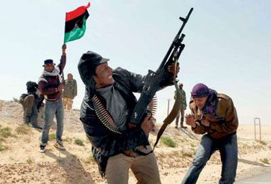 Libyan rebels celebrate in the city of Ajdabiya, south of Benghazi, eastern Libya, Saturday. Libyan rebels regained control of the eastern gateway city of Ajdabiya Saturday after international airstrikes crippled Moammar Gadhafi's forces, in the first major turnaround for an uprising that a week ago appeared on the verge of defeat. (AP Photo)