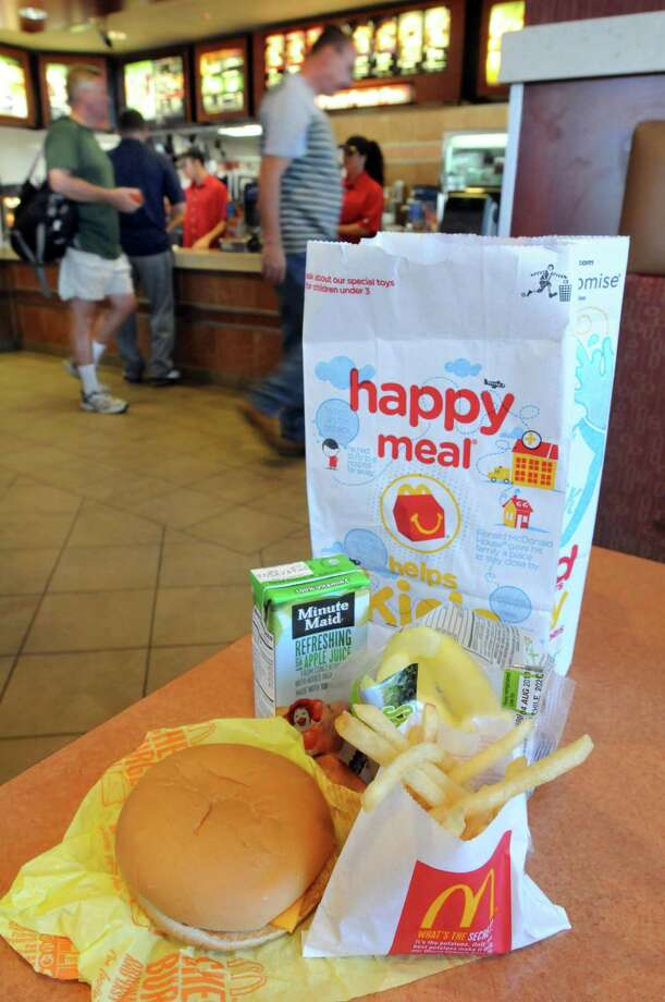 A Happy Meal sites on a table as customers place orders at the McDonald's on Washington Street in North Haven Tuesday. The fast food chain said it will make its Happy Meals healthier, adding apples and reducing the french fry portion sizes. (Photo by Mara Lavitt/New Haven Register)