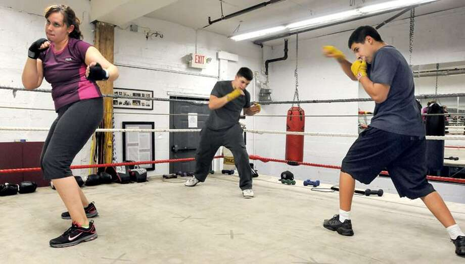 Left to right: Gina Walerysiak of Wallingford, Arthur Natalino of East Haven and Christian Valentin of New Haven shadow box for three minute drills at the Pugilist College Boxing Academy. Mara Lavitt/Register  11/21/11