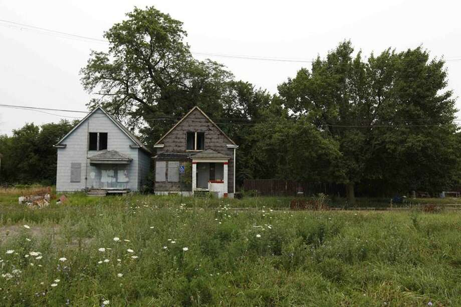 Two abandoned homes sit on an overgrown lot in a Detroit neighborhood Wednesday. Associated Press Photo: AP / AP