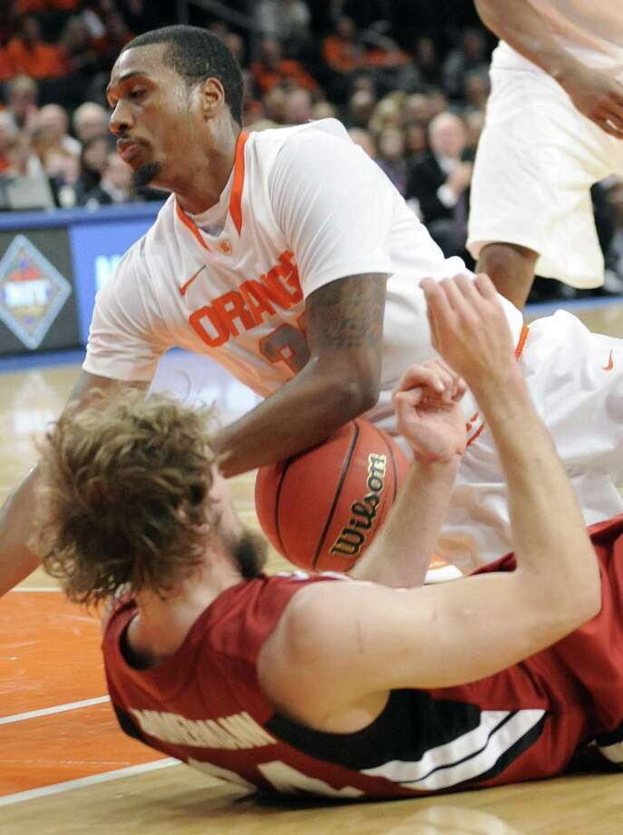 Syracuse forward Kris Joseph, right, falls on Stanford forward Andrew Zimmerman during the first half of the championship game in the NIT Season Tip-Off college basketball tournament on Friday, Nov. 25, 2011 at New York's Madison Square Garden.  (AP Photo/Bill Kostroun) Photo: AP / FR51951 AP