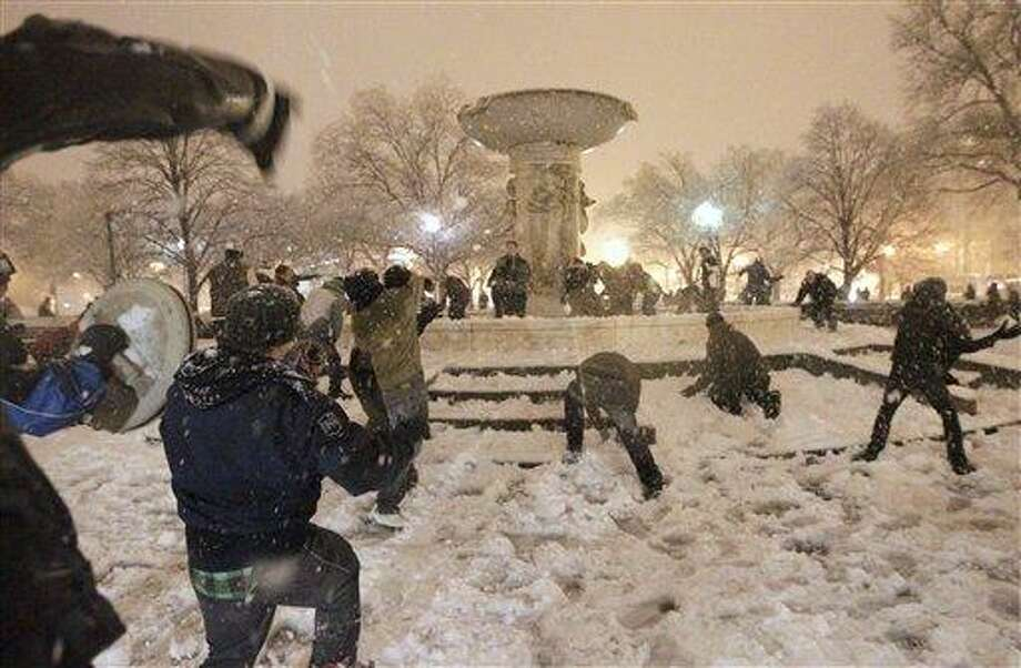 A snowball fight breaks out at Dupont Circle in Washington in the still-falling snow, Wednesday, Jan. 26, 2011. (AP Photo/Pablo Monsivais) Photo: AP / AP