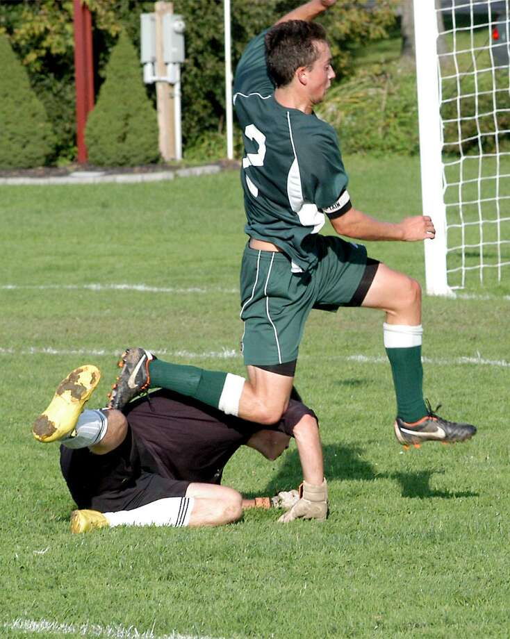 Dispatch Staff Photo by DAVID M. JOHNSONHamilton's Drew Thompson jumps over Clinton goalkeeper Rob Larkin after a breakaway in a Center State Conference match Monday, September 26, 2011 in Clinton.