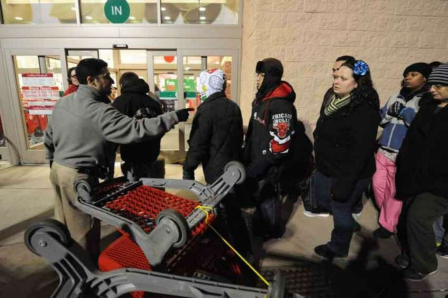 A Target employee who asked not to be identified directs an allotted number of customers through the barricade in front of the North Haven store in an effort to control the thousands of people who lined up and waited, some as many as nine hours, to begin the holiday shopping season. V.M. Williams/Register