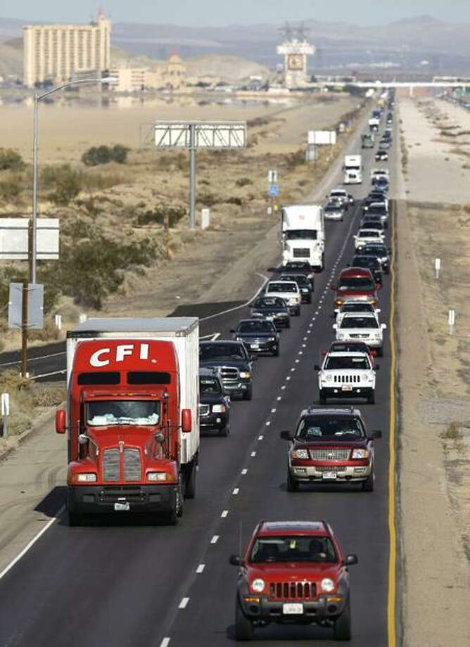 In this Nov. 23, 2011, photo, motorists head south toward Los Angeles on Interstate 15 just across the Nevada state line near Primm, Nev.  The average price for a gallon of gas has fallen 7 cents in just a week to $3.31. The discount is 13 cents in the past month. That's because, holiday shopping aside, motorists tend to drive less in the colder months. And refiners are making cheaper winter blends of gas at this time of year. (AP Photo/Julie Jacobson, File) Photo: AP / AP