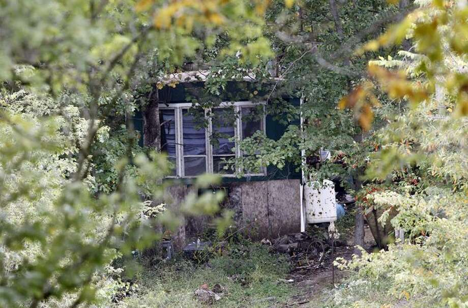 Trees and brush surround the mobile home of Roy Napier, where four people were found dead in rural Franklin County near Laurel, Ind. on Monday, Sept. 26, 2011. A fifth person was found dead across the street. Associated Press Photo: AP / Copyright 2011 AJ Mast, aj@ajmast.com, 317.727.9251