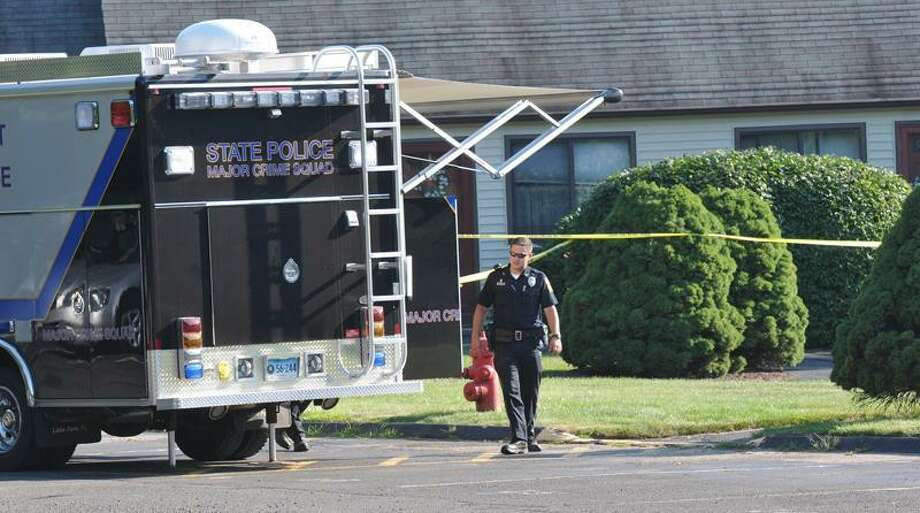 A police officer walks next to a State Police mobile crime lab outside an apartment where a woman's body was found Saturday at 19 Danny's Way in Wallingford. Peter Casolino/Register