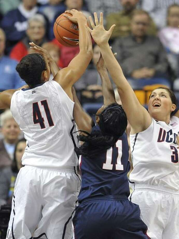 Connecticut's Kiah Stokes (41) blocks a shot from Fairleigh Dickinson's Desiree Crawford (11) as Stefanie Dolson, right, defends in the first half of an NCAA college basketball game in Storrs, Conn., Friday, Nov. 25, 2011. (AP Photo/Jessica Hill) Photo: AP / AP2011