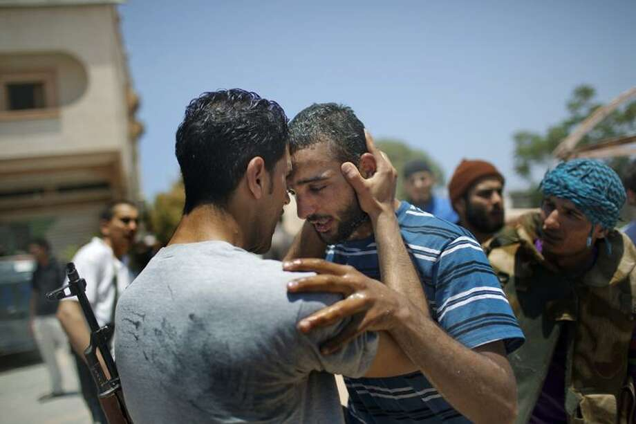 Rebel fighters mourn the dead at the front line between them and Moammar Gadhafi forces. Associated Press Photo: AP / AP