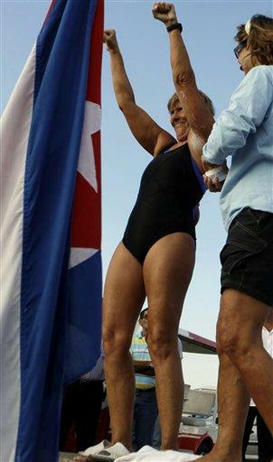 U.S. swimmer Diana Nyad greets her support team before beginning her swim from Cuba to Florida at the Hemingway Marina in Havana, Cuba, Friday Sept. 23, 2011. Endurance athlete Nyad is preparing for a second attempt to swim from Cuba to Florida and set a world record at the age of 62. The Los Angeles woman fell short in a previous attempt at the swim last month, calling it off after 29 hours in the water and about halfway through the 103-mile (166-kilometer) journey. (AP Photo/Javier Galeano) Photo: ASSOCIATED PRESS / AP2011