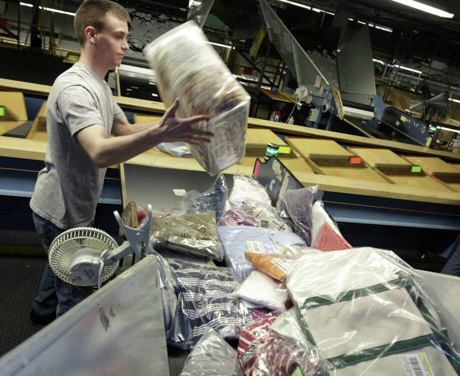 Justin Reil prepares merchandise for shipping at a facility at L.L. Bean in Freeport, Maine Thursday. The company is offering permanent, no-strings-attached free shipping. (AP Photo/Pat Wellenbach) Photo: ASSOCIATED PRESS / AP2011