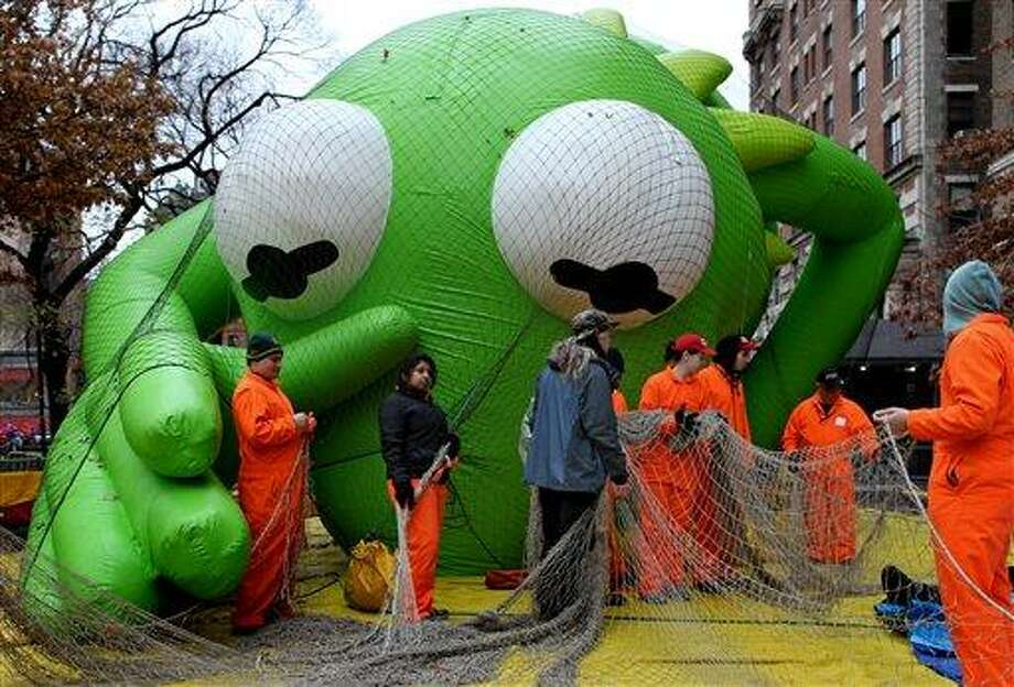The Kermit the Frog balloon seems to reach out towards balloon handlers with Macy's department store's 85th annual Macy's Thanksgiving Day Parade as they work on another one of 15 giant helium balloons and 44 novelty and specialty balloons Wednesday, Nov. 23, 2011 that will be featured in Thursday's parade in New York. (AP Photo/Craig Ruttle) Photo: AP / FR61802 AP
