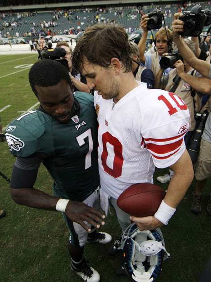 Philadelphia Eagles' Michael Vick, left, shows his hand to New York Giants' Eli Manning after an NFL football game on Sunday, Sept. 25, 2011, in Philadelphia. Vick left with a broken right hand in the fourth quarter and New York won 29-16. (AP Photo/Matt Slocum) Photo: AP / AP2011