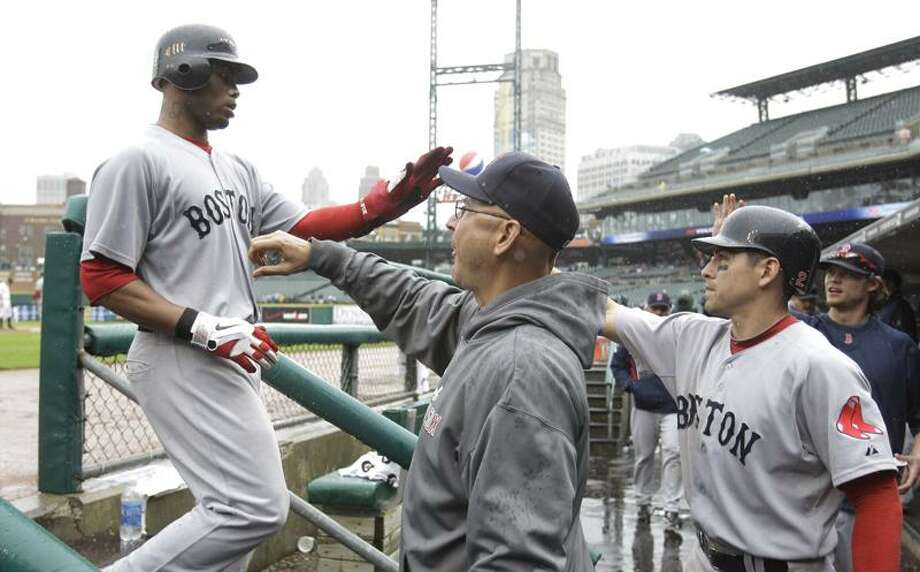 Boston Red Sox's Carl Crawford, left, is congratulated by coach Terry Francona, center, after scoring from third on a Josh Reddick single during the eighth inning of a baseball game against the Detroit Tigers in Detroit, Thursday, May 26, 2011. (AP Photo/Carlos Osorio) Photo: AP / AP2011
