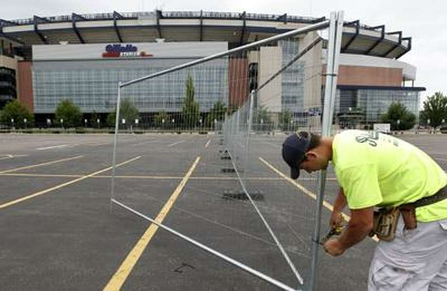 Worker Dell Goncalves, of Medford, Mass., constructs a fence in a parking lot at Gillette Stadium football and soccer arena, in Foxborough, Mass., Monday, July 25, 2011. NFL owners and players agreed early Monday to the terms of a deal to end the lockout, and players were expected to begin their voting process later in the day, two people familiar with the negotiations told The Associated Press. (AP Photo/Steven Senne) Photo: AP / AP