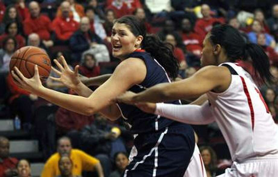 Connecticut's Stefanie Dolson, left, tries to control the ball as Rutgers' Khadijah Rushdan defends during the first half of an NCAA college basketball game on Wednesday, Jan. 26, 2011, in Piscataway, N.J. (AP Photo/Mel Evans) Photo: AP / AP