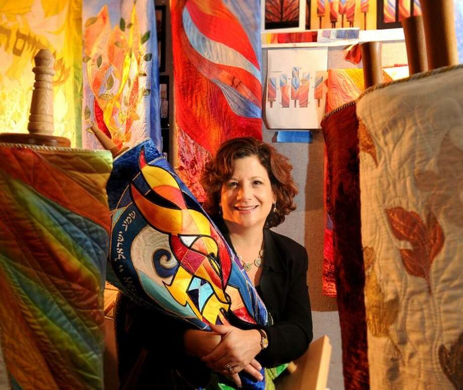 Jeanette Kuvin Oren, an artist who specializes in  Judaic artwork, sits in her Woodbridge studio with examples of Torah covers that she has created for clients worldwide.