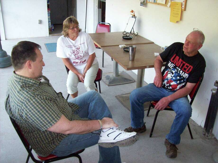 Retired United States Army Maj. John Ready, left, meets with Munnsville American Legion Post 54 Commander Tom Hollingsworth, right, and his wife LuAnn Hollingsworth Wednesday to discuss Ready's Veteran Images project. (Photo by MIKE JAQUAYS)