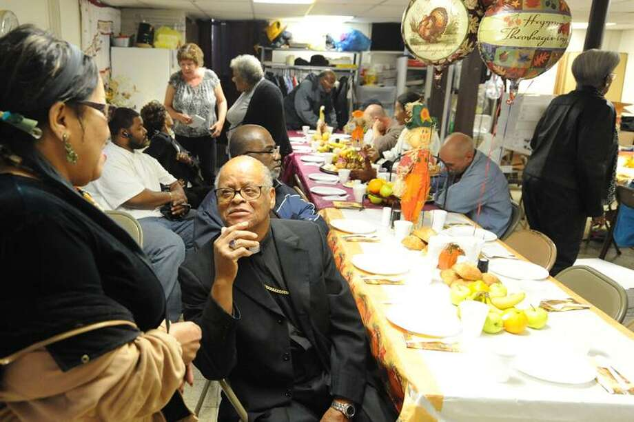 Bishop Robert Stallings Sr., seated, greets a diner as she enters the dining room at the Church of God and Saints of Christ in New Haven Thursday. VM Williams/Register