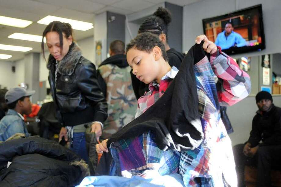 Angie Biggs and Jamal Dailey look over the selection of coats that have been donated by teens to help the less fortunate at the Headz Up Barbaershop on Whalley Ave in New Haven Thanksgiving Day 2011. vmWilliams 11.24.11