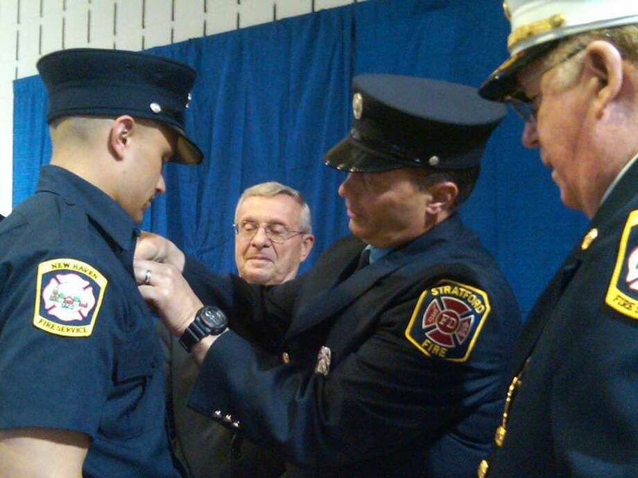 Ryan Almeida has his badge pinned on by his father, Greg, a Stratford firefighter.