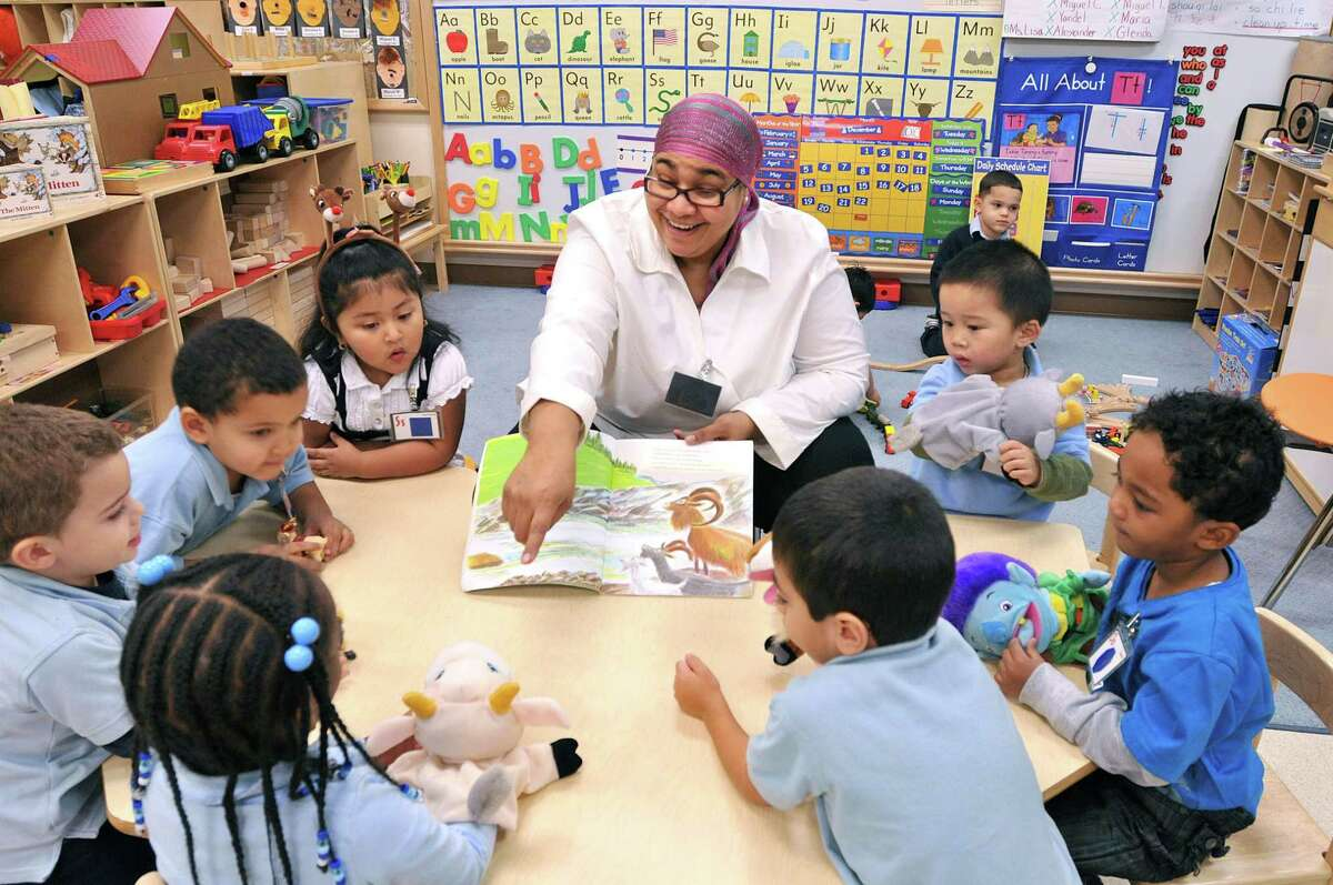 New Haven-- Preschool teacher Elizabeth Reyes works with her students at the Christopher Columbus Family Academy. Reyes is featured on the cover of the December/January issue of