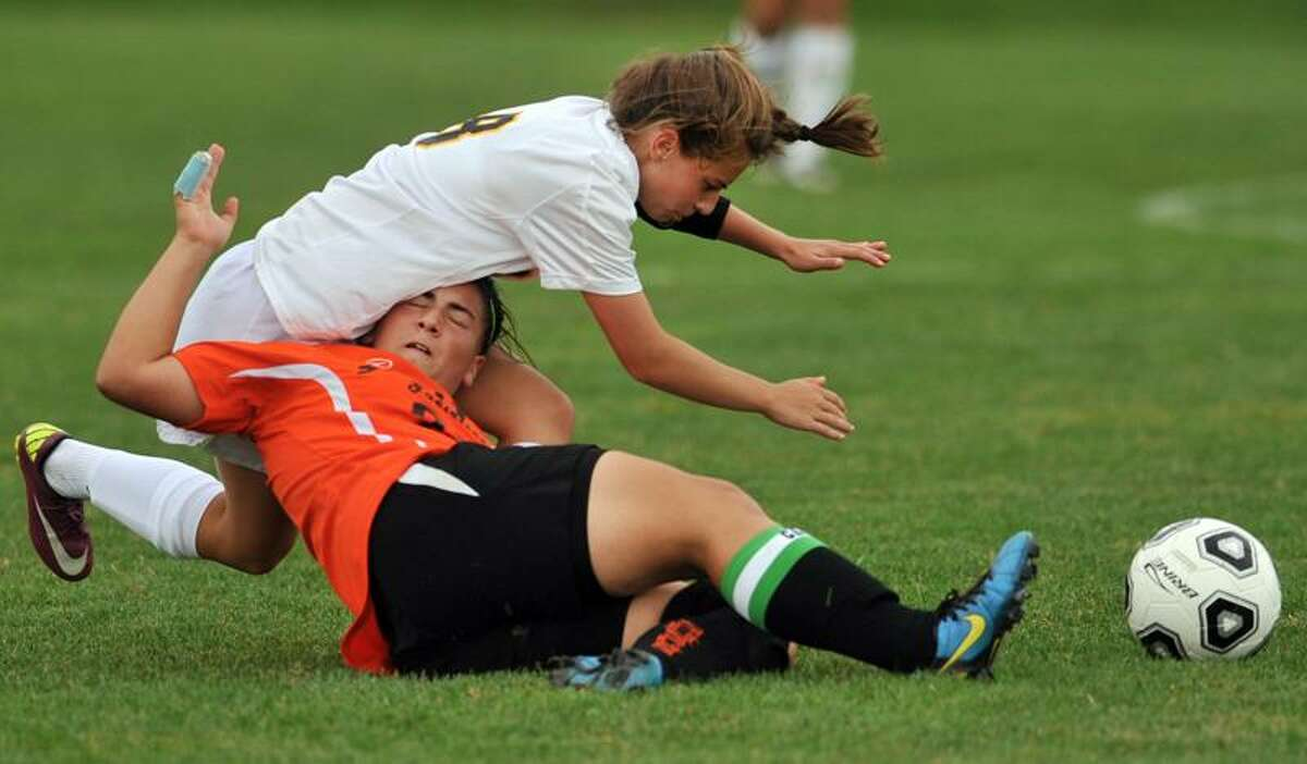 Amity's Cassie Giza, left, falls over Jessica Hartmayer of Shelton during first-half soccer action that resulted in a 1-1 tie. Photo by Peter Hvizdak / Register