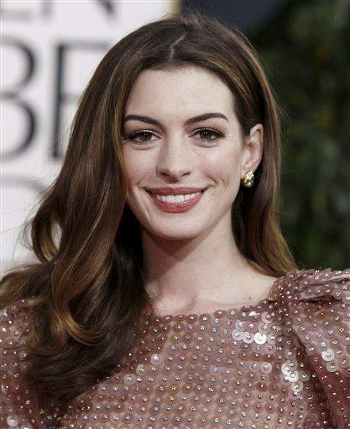 """FILE - In this Jan. 16, 2011 file photo, Anne Hathaway arrives at the Golden Globe Awards in Beverly Hills, Calif. Warner Bros. on Wednesday, Jan. 19 announced that Hathaway will play the role of Selina Kyle and her alter ego, Catwoman, in """"The Dark Knight Rises,"""" Christopher Nolan's latest film in the Batman saga. (AP Photo/Matt Sayles, File)"""