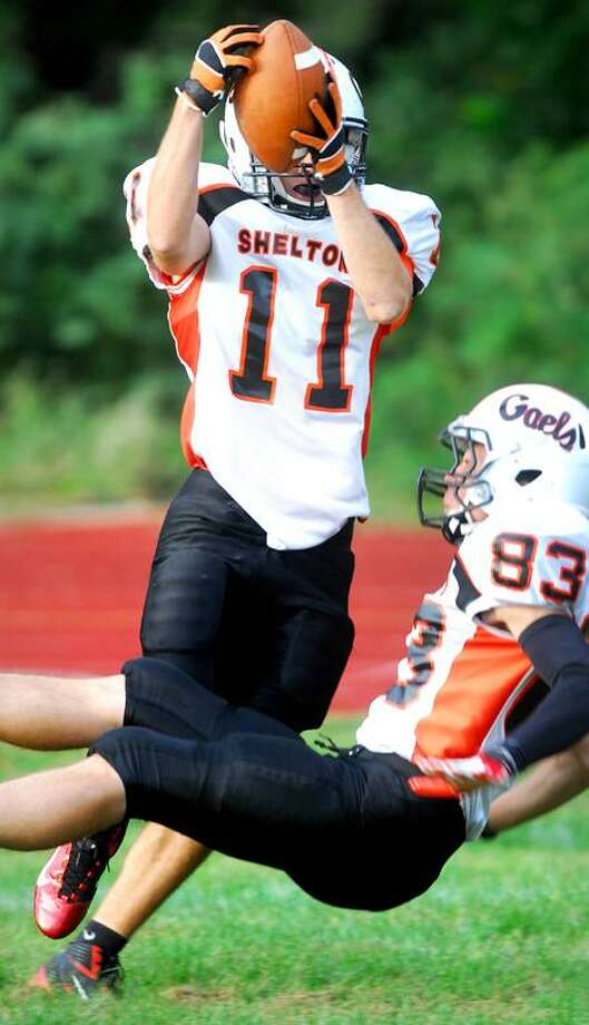 Shelton's Eddie Kochiss (left) comes down with a touchdown reception in the second half against Wilbur Cross. Andrew Kalinowski of Shelton is at right. Photo by Arnold Gold/New Haven Register