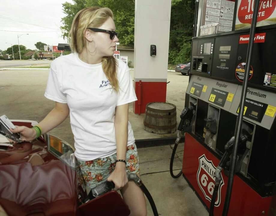 In this June 22 photo, Susan Bridges pumps gas into her car at a Little Rock, Ark., Conoco Phillips station. Companies paid less for raw materials and factory goods in June, evidence that inflation pressures are weakening as gas prices fall. (AP Photo/Danny Johnston) Photo: ASSOCIATED PRESS / AP2011