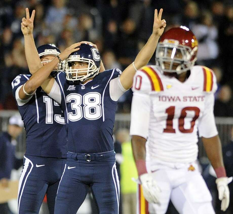 Connecticut's Dave Teggart, center, celebrates his 52 yard field goal with teammate Chad Christen as Iowa State's Jacques Washington looks on during the first half in their NCAA football game, Friday, Sept. 16, 2011, in East Hartford, Conn. (AP Photo/Fred Beckham) Photo: AP / FR153656 AP