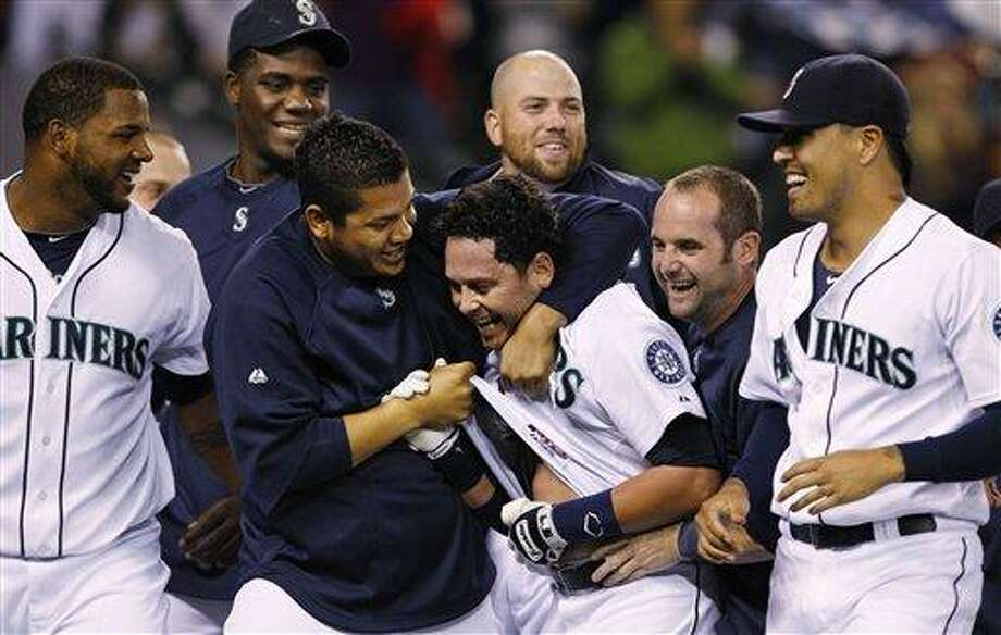 Seattle Mariners' Luis Rodriguez, center, is put into a playful headlock by Felix Hernandez as other teammates cheer Rodriguez following his game-winning home run against the New York Yankees  in the 12th inning of a baseball game Wednesday, Sept. 14, 2011, in Seattle. The Mariners won 2-1. (AP Photo/Elaine Thompson) Photo: ASSOCIATED PRESS / AP2011
