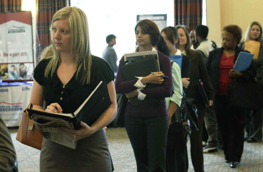 Annelie Ingvarsson, left, waits in line to talk to potential employers during a National Career Fairs job fair Wednesday in Bellevue, Wash. The number of people applying for unemployment benefits last week jumped to the highest level in three months, a sign that layoffs could be increasing. (AP Photo/Ted S. Warren) Photo: ASSOCIATED PRESS / AP2011
