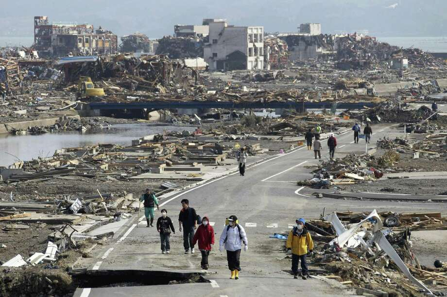 People walk a road between the rubble of destroyed buildings in Minamisanriku town, Miyagi Prefecture, northern Japan, Monday, March 14, 2011, three days after a powerful earthquake-triggered tsunami hit the country's east coast. (AP Photo/The Yomiuri Shimbun, Tsuyoshi Matsumoto) Photo: ASSOCIATED PRESS / AP2011