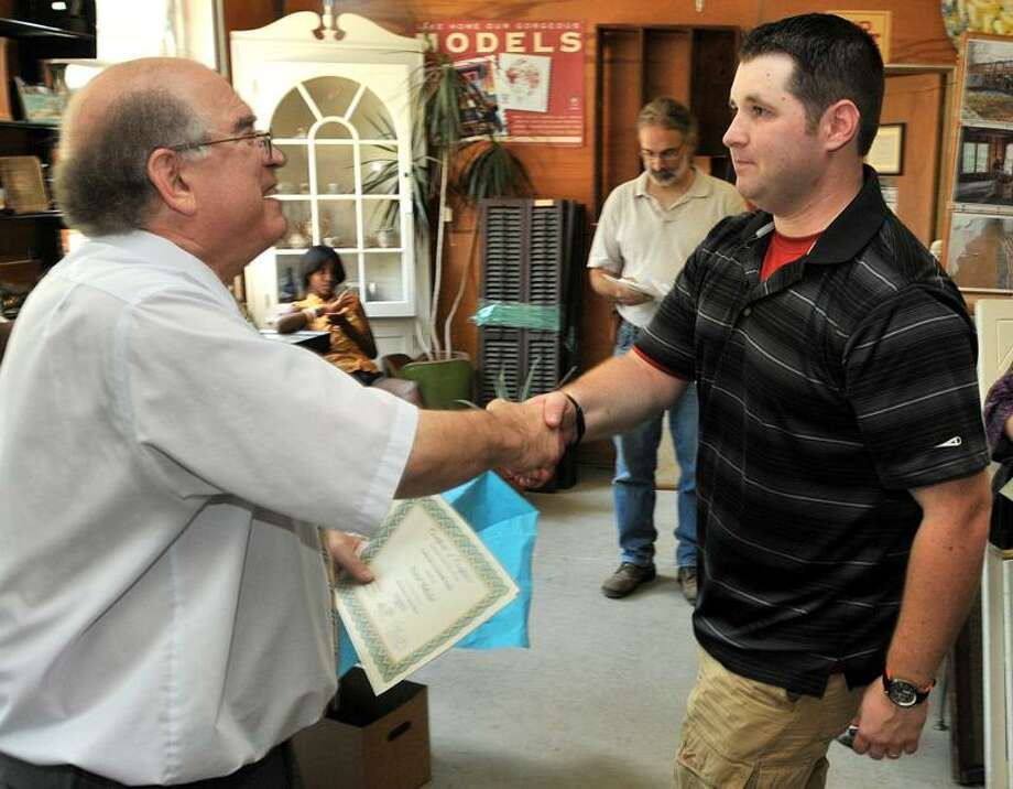 Daniel Blakeslee, right, gets his certificate of completion of the Deconstruction & Material Reuse Program from Gateway Community College-North Haven's Center for a Sustainable Future's David Cooper Friday at Urbanminers in Hamden. Brad Horrigan/Register