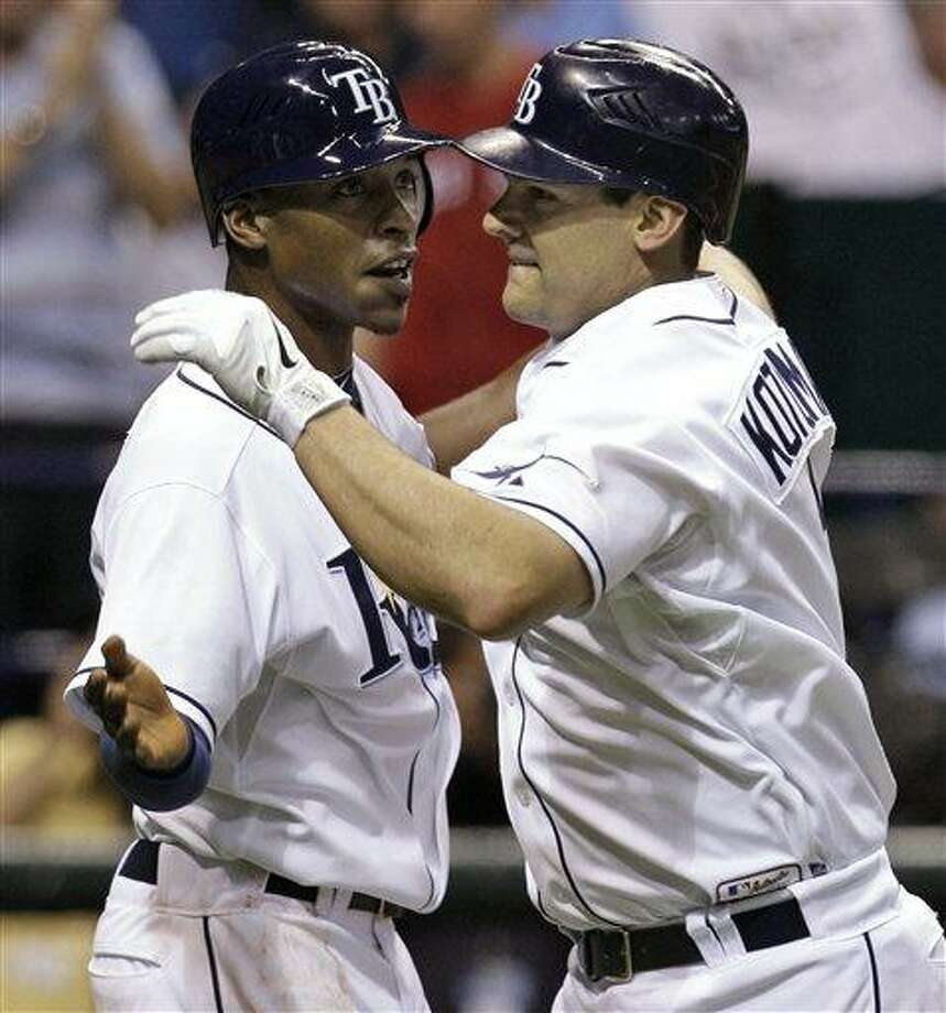 The Tampa Bay Rays' Casey Kotchman, right, high-fives B.J. Upton after Kotchman hit a two-run, sixth-inning home run off Boston Red Sox relief pitcher Dan Wheeler on Friday. The Rays won 9-6. (AP photo) Photo: AP / AP