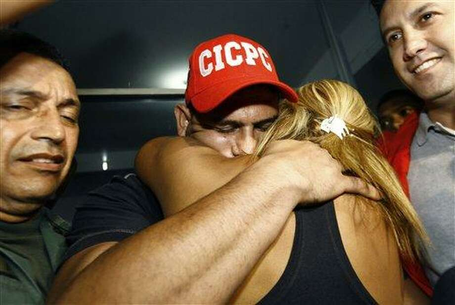 Washington Nationals' catcher Wilson Ramos is hugged by a relative at the Criminal Police ( CICPC ) headquarters  in Valencia, Venezuela, Saturday, Nov. 12, 2011. Venezuelan police commandos rescued Ramos and arrested three of his abductors Friday, two days after he was kidnapped.  At right is Venezuela's Justice Minister Tareck El Aissami.(AP Photo/Lexander Loiza) Photo: AP / Copyright 2011 The Associated Press. All rights reserved. This material may not be published, broadcast, rewritten or redistributed.