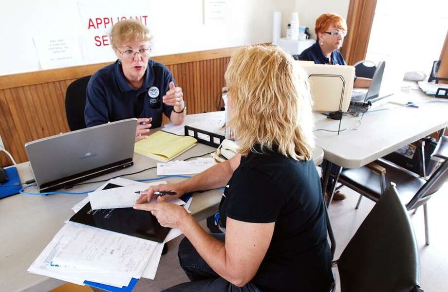 Fema official Mari Ludwig, rear, talks with Sally Hopkins of East Haven Thursday, helping her put together her application for aid. FEMA officially came to East Haven Thursday to provide assistance following Hurricane Irene. VM Williams/Register